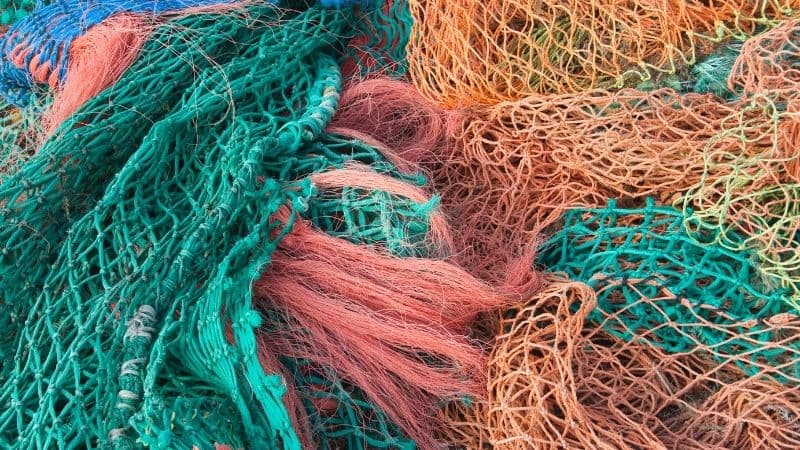 Image of tangled up fishing nets. They are in bright shades of green, blue, red and orange